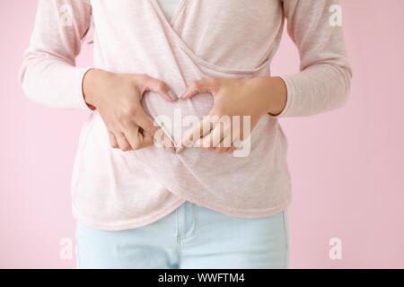 Jeune femme enceinte faire coeur avec ses mains sur un fond de couleur, gros plan Banque D'Images
