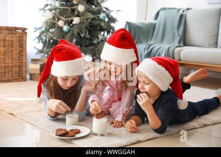 Heureux les petits enfants au Père Noël chapeaux de manger des cookies avec du lait à la maison Banque D'Images
