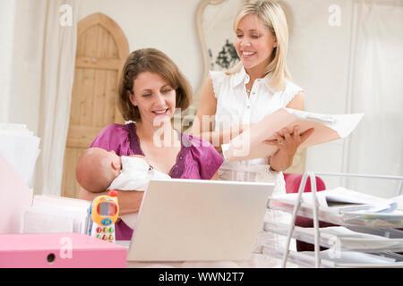 Deux femmes et un bébé dans le bureau d'accueil avec coffre Banque D'Images
