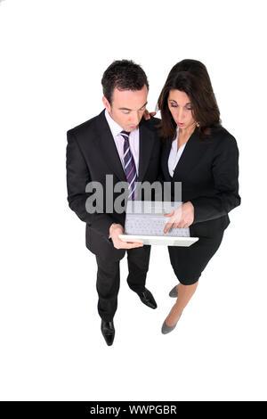 Business couple surpris par quelque chose sur leur ordinateur portable Banque D'Images