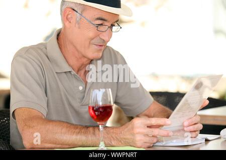 Monsieur âgé assis dans cafe boire dans un verre de vin rouge Banque D'Images