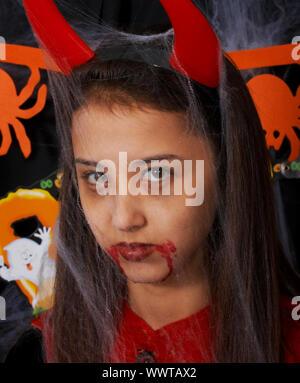 Costume Halloween Girl habillé comme le diable avec du sang autour de sa bouche Banque D'Images
