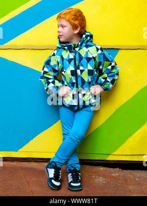 Petit garçon à la mode. Red-haired beau gosse. Model wearing trendy jacket posing contre mur rayé en bonne automne-printemps Banque D'Images