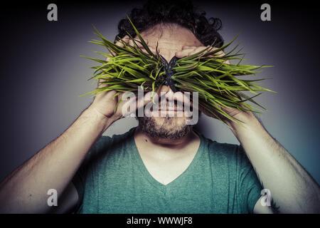 Notion de dépendance aux drogues, l'homme avec l'herbe dans les yeux avec geste de bonheur