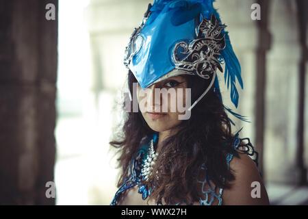 Gothique, belle femme latine habillés en costume et le casque blue feather simulant un oiseau exotique dans un lieu à l'automne Banque D'Images