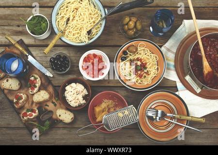 Des plats italiens traditionnels. Les pâtes spaghetti avec sauce tomate, olives et garnir de vin sur le woo Banque D'Images