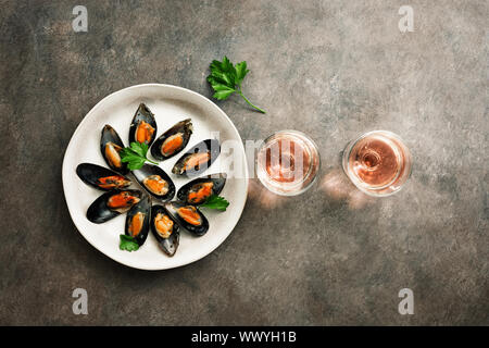 De délicieux fruits de mer moules aux épices, du persil et deux verres de vin mousseux rose dans une rangée, rustique foncé arrière-plan. Haut de la vue, télévision lay, copy space
