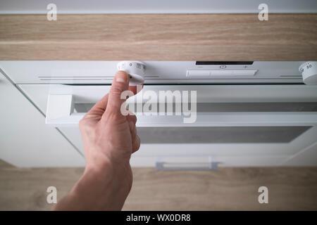 Part en poussant un bouton d'alimentation sur un panneau de contrôle d'un four électrique Banque D'Images