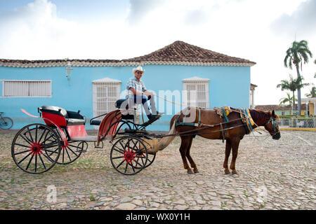 Pour les cavaliers en attente de cow-boy avec son cheval et sa voiture sur la Plaza Mayor, l'UNESCO, Trinidad, Cuba, Antilles, Caraïbes, Amérique Centrale Banque D'Images