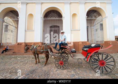 Cheval et le transport dans la Plaza Mayor et l'église de la Sainte Trinité, l'UNESCO, Trinidad, Cuba, Antilles, Caraïbes, Amérique Centrale Banque D'Images