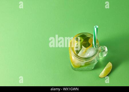 Des boissons froides de Mojito mousseux agrumes naturelles avec des pailles en plastique sur un fond vert. Vue d'en haut. Copier sp Banque D'Images