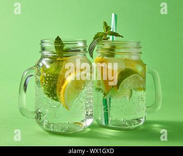 Titre alcoométrique naturel froid mojito avec des bulles d'air. Deux faits à la main en verre pot Mason avec cocktail sur un fond vert. Banque D'Images