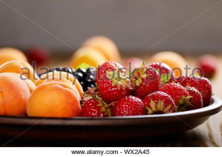 Venu de bleuets biologiques des abricots et des fraises dans la plaque d'argile sur table en bois Banque D'Images