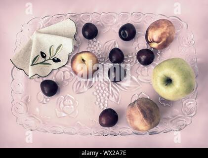 Les prunes, les pêches, les pommes sur un plateau de verre Banque D'Images