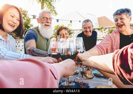 Happy friends toasting with verres à vin au dîner sur le patio - Maturité s'amusant ensemble de salle à manger à l'extérieur Banque D'Images