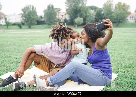 Heureux de prendre une famille africaine avec selfies smart mobile phone appareil photo dans un parc public en plein air - La mère et le père s'amusant avec leur fille Banque D'Images