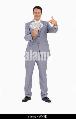 Portrait d'un homme montrant beaucoup de dollars contre fond blanc