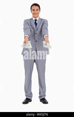 Portrait d'un homme donnant à beaucoup de dollars contre fond blanc