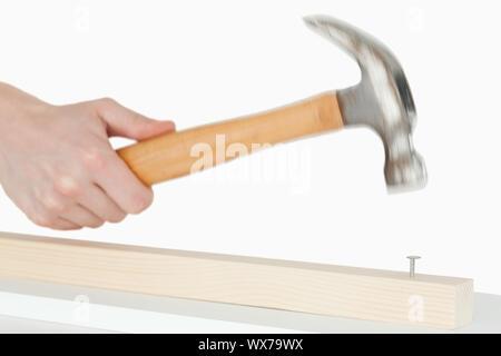 Main tenant un marteau pour extraire un clou sur un fond blanc. Banque D'Images