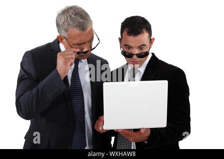 Les hommes d'affaires portant des lunettes de soleil à la recherche à un ordinateur portable