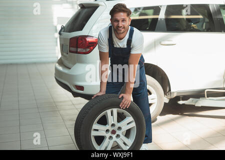 Young handsome mechanic working in car service services pneus fixation . Banque D'Images