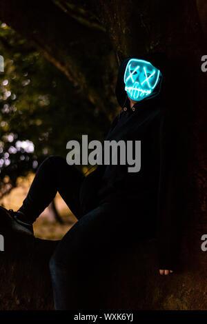 Personne isolée assis sur une branche portant masque d'halloween light up creepy Banque D'Images