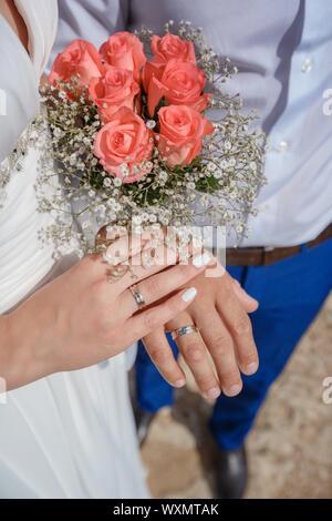 Senior couple holding hands and afficher les anneaux de mariage, bouquet de mariage sur l'autel de l'église. Les mains et les joints toriques de mariage bouquet Banque D'Images
