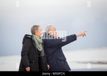 Happy mature couple walking on beach in autumn Banque D'Images