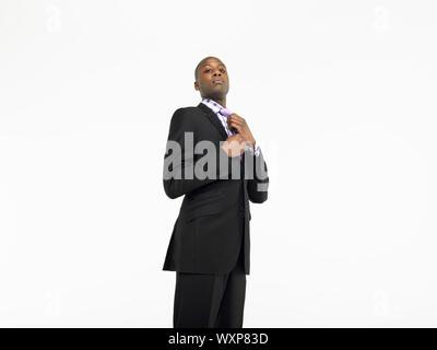 Portrait of businessman adjusting tie over white background Banque D'Images