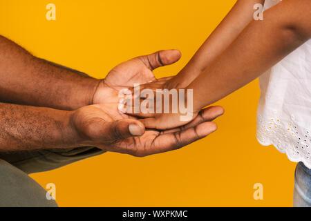 Papa africain tenant la main de sa petite fille