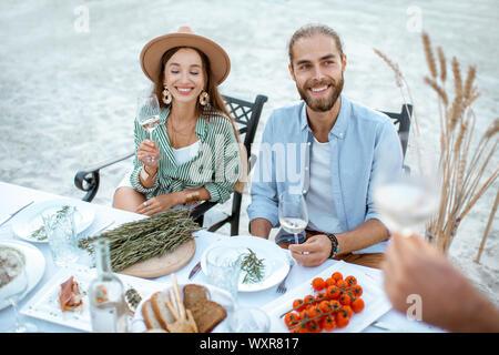 Jeune couple avec des amis à manger à la table magnifiquement décorée sur la plage près du lac Banque D'Images
