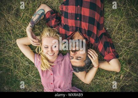 Jeune couple dans l'amour. Deux personnes, blonde et barbu, allongé sur l'herbe verte. Petite amie et petit ami de jouer les uns avec les autres cheveux.