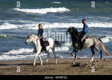Femme Homme, Couple riding horse on a beach Banque D'Images