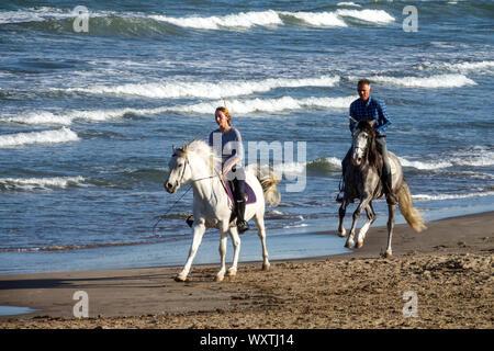 L'homme et de la femme de l'équitation sur la plage, Costa Blanca, Espagne Banque D'Images