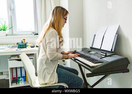 Belle Jeune femme jouant du piano à la maison