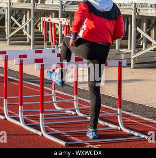 Une fille de l'école d'athlétisme est en préchauffage pour sa course de haies en marchant sur des obstacles sur une piste rouge dans son sweatsuit. Banque D'Images
