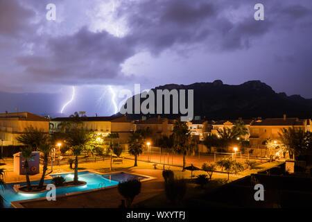 El Verger,27,2019-Spain-August un foudre de stromy nuages sur un village avec une piscine et les montagnes Banque D'Images