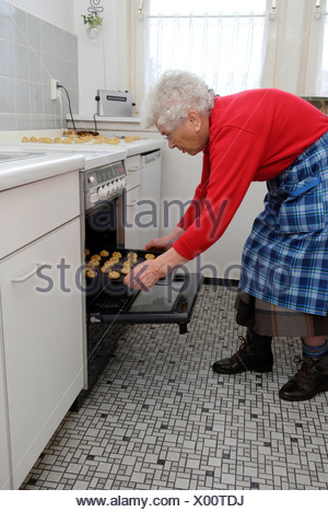 Old woman baking cookies Banque D'Images