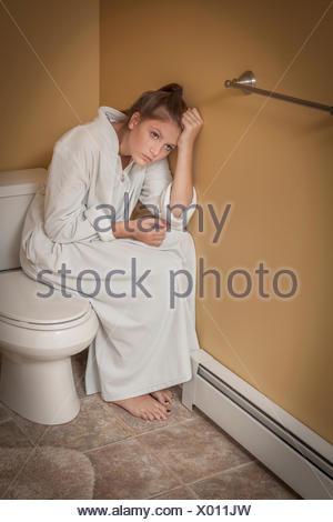 Teenage girl sitting dans la salle de bains sur le siège des toilettes à la malheureuse Banque D'Images