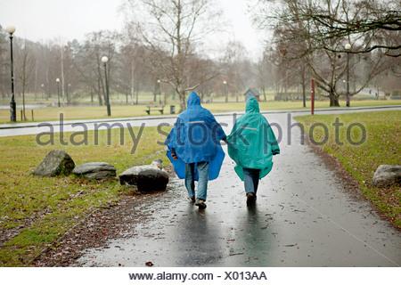 Senior couple in vêtements imperméables walking through park Banque D'Images