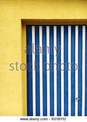 Porte jaune à rayures bleu sur House Banque D'Images