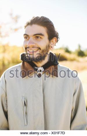 Portrait de jeune homme, souriant, à l'extérieur Banque D'Images
