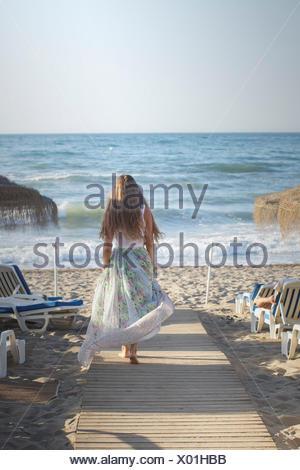 Jeune femme marchant le long trottoir de bois vers la plage Banque D'Images
