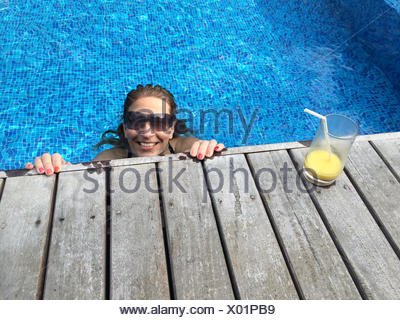 Woman with cocktail relaxing in swimming pool Banque D'Images