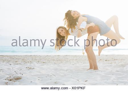 Deux jeunes amis féminins donnant dos à dos ascenseurs on beach Banque D'Images