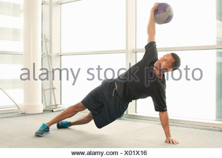 L'homme s'étend à l'aide de boule d'exercice Banque D'Images