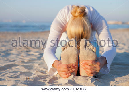 Woman doing yoga étirement de prière sur la plage Banque D'Images