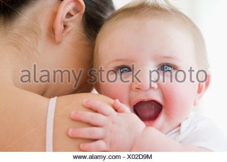 Rire bébé sur l'épaule de la mère Banque D'Images