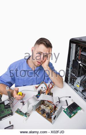 Portrait de fatigué ingénieur en informatique avec des pièces de l'unité centrale Banque D'Images