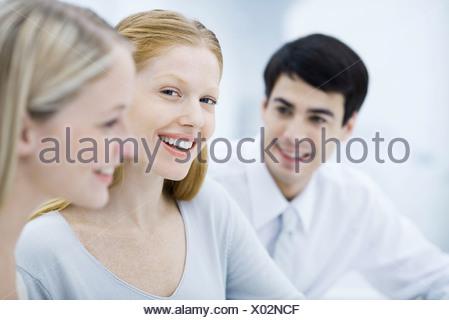 Jeune professionnel femme entre deux collègues, smiling at camera Banque D'Images
